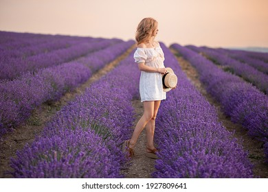 Side view of la blonde young lady in delicate white dress looking aside while sitanding alone among aromatic lavender flowers on meadow