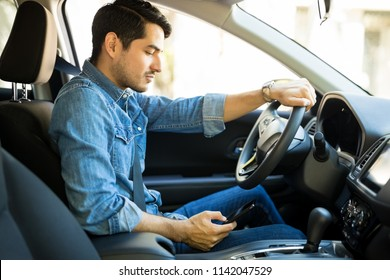 Side view of latin man driving a car and reading text message on his mobile phone