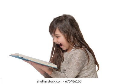 Side view of laughing long haired little girl leaning over an open book