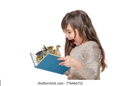 Side view of laughing surprised long haired little girl holding an open book with peeking animals . All is on the white background.