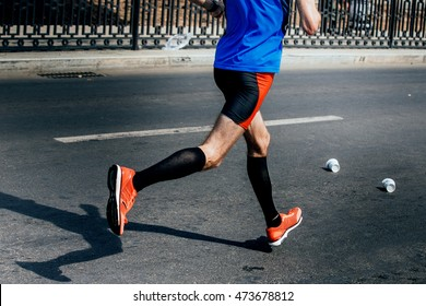 side view of legs of male athlete in compression socks running sports race