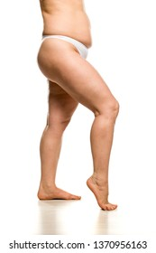 Side view of legs and waist of overweight woman on white background