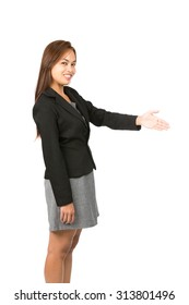 Side view of light brown haired Asian woman in black, gray business clothes smiling greeting, offering handshake turning head looking at camera on deal. Thai national of Chinese origin.