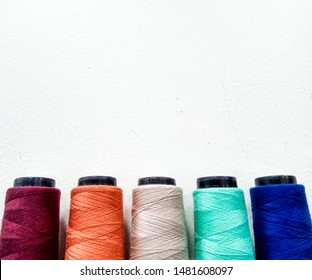 Side view of lined up five cones of colourful thread, isolated in white background. Thread colour red, orange, khaki, mint and dark blue. Space for text