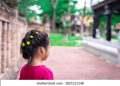 Side view of little asian girl in red dress with beautiful hair and yellow flower walking in the park