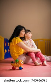 Side view of little beautiful disabled girl who sitting on lap of young cheerful mother in the room and toy in the foreground