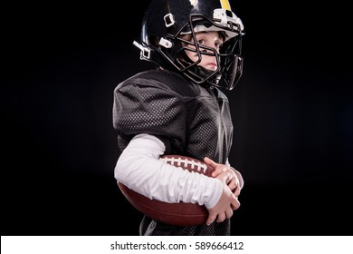 Side view of little boy american football player in uniform holding ball isolated on black
