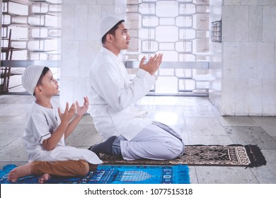 Side view of little boy with his father praying together after doing Salat in the mosque