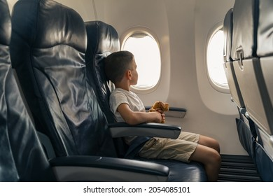 Side view of little boy looking aerial view of sky and cloud outside airplane window. Copy space