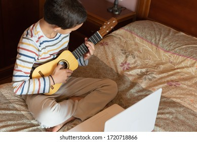 Side view of a little boy playing timple at home. The timple is a typical musical instrument from the Canary Islands, Spain