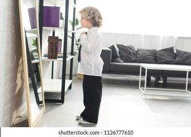 side view of little boy tying necktie over white shirt in front of mirror at home