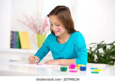 side view of little girl painting. cute pupil sitting and drawing pictures