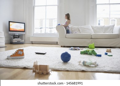Side view of a little girl watching television with toys on floor in foreground