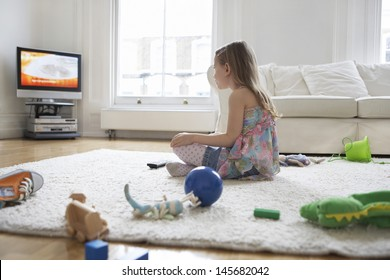 Side view of a little girl watching television with toys on floor