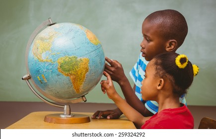 Side view of little kids pointing at globe in classroom