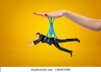 Side view of little man in suit hanging on blue sticky slime stuck to big woman's hand above on yellow background. Unfair manipulation. Puppets and their masters. Possessive relationship.
