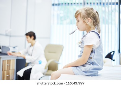 Side view of little patient sitting on couch in doctors office and holding thermometer in mouth