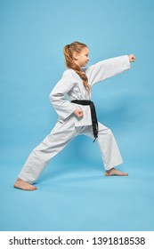 Side view of little strong girl in kimono standing in karate stance in studio. Pretty female teenager exercising and practising martial arts on blue isolated background. Concept of sport and judo.