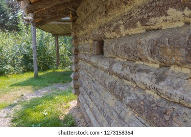 Side view of a log cabin wall with window