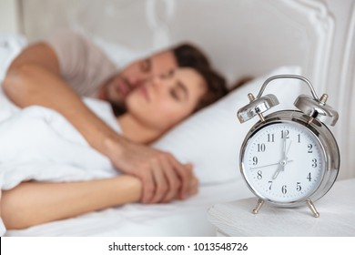 Side view of Lovely couple sleeping together in bed with alarm clock. Focus on alarm clock