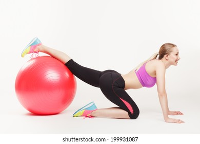 side view of lovely girl doing an exercise with a pink gym ball over white background