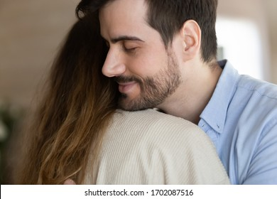 Side view loving young bearded man embracing wife after reconcile, close up head shot. Affectionate married couple cuddling, enjoying love sweet tender moment together indoors, feeling thankful.