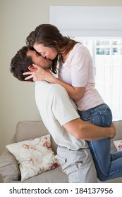 Side view of a loving young couple kissing in the living room at home