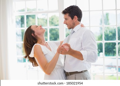 Side view of a loving young couple dancing at home