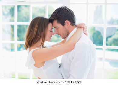 Side view of a loving young couple with arms around at home