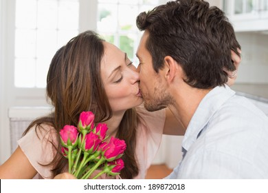 Side view of a loving young couple kissing with flowers in hand at home