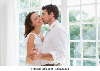 Side view of a loving young man kissing woman at home