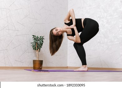 Side view low angle of slim female standing barefoot on mat in Revolved Chair pose and doing yoga at home while balancing and looking at camera