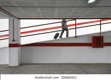 Side view low section of a businessman walking up ramp in parking garage with luggage
