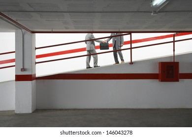 Side view lowsection of two businessmen exchanging briefcase on ramp in parking garage