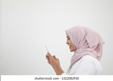 side view malay woman with tudung using smart phone on the white background