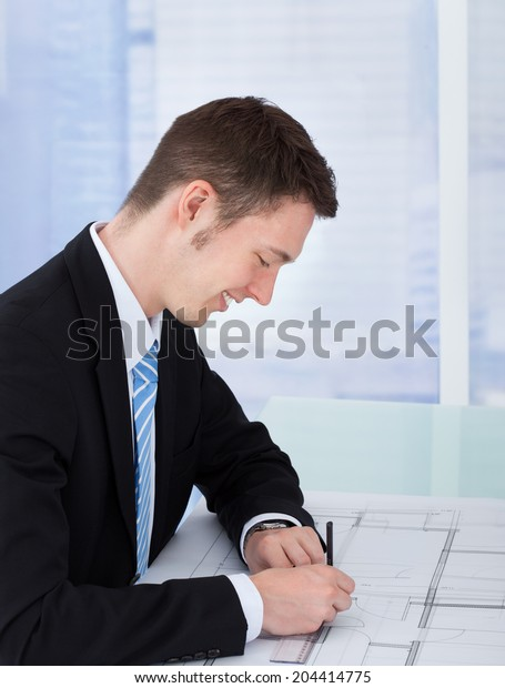 Side view of male architect working on blueprint at desk in office