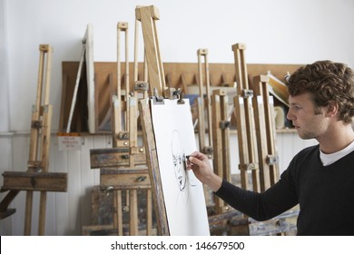 Side view of a male artist drawing charcoal portrait in studio