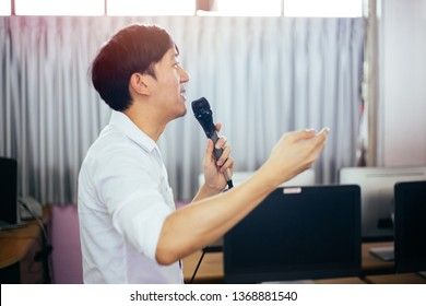 Side view of male Asian businessman speaking and making a lecture in public speaking event in the room