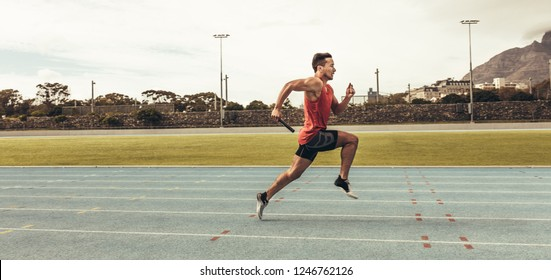 Side view of a male athlete sprinting on a running track in a track and field stadium holding a baton. Male runner training on a running track.