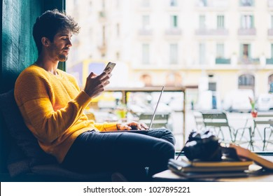 Side view of male blogger browsing profile in networks on smartphone via 4G internet connection resting in stylish coffee shop with modern laptop computer.Young man chatting online on mobile phone
