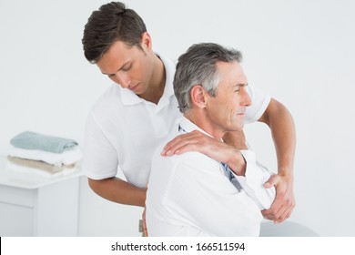 Side view of a male chiropractor examining mature man at office