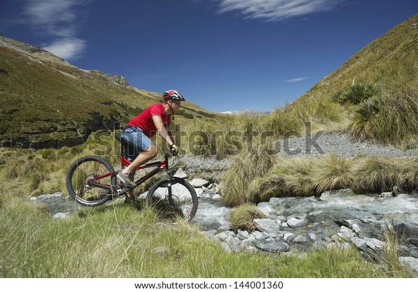 Side view of a male cyclist riding through rocky field
