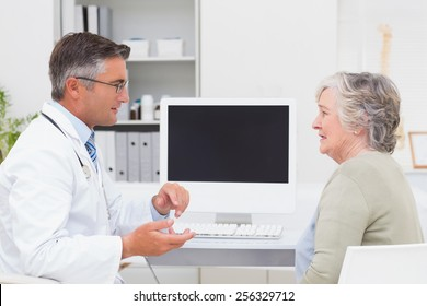 Side view of male doctor conversing with senior patient at table in clinic