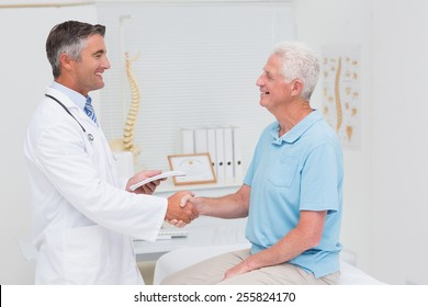 Side view of male doctor and senior patient shaking hands in clinic