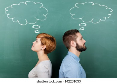 Side view of male and female professors with thought bubble on chalkboard