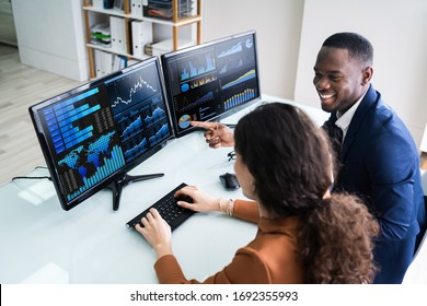 Side View Of Male And Female Stock Market Broker Analyzing Graphs On Laptop At Workplace - Shutterstock ID 1692355993