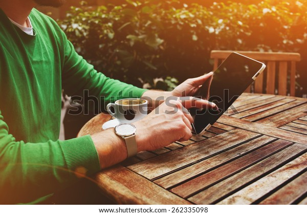 Side view male freelancer sitting on the terrace with cup of coffee and touch screen tablet while having a break, man's hands typing message on digital tablet sitting at cafe table with plants, flare