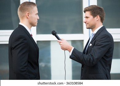 Side view of male journalist interviewing businessman outdoors