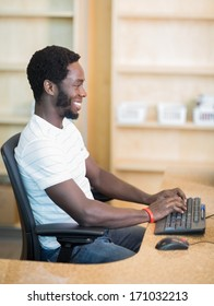 Side view of male librarian working on computer at library desk
