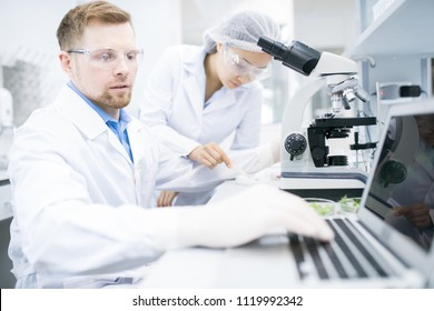 Side view of male microbiologist in white laboratory coat typing on laptop keyboard data received during testing of food nutrition properties under microscope with female assistant on background.